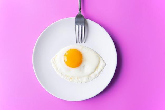 Prima colazione, uovo fritto, tuorlo, omelette e forcella sul piatto bianco con la tavola di colore, immagine creativa