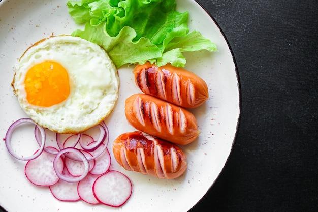 Colazione, uova fritte salsicce e verdure