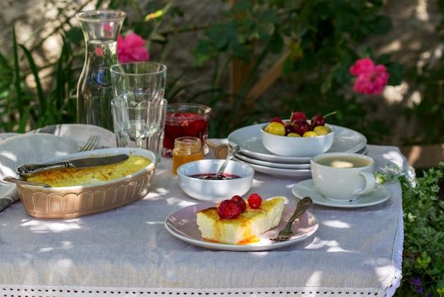 Colazione in giardino da casseruole, frutti di bosco, salse e bevande.