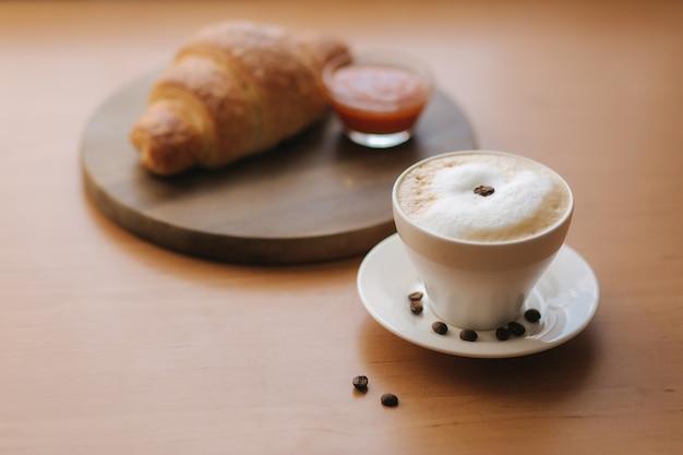 Colazione a casa. cappuccino con croissant vuoti. mattina con caffè. marmellata di albicocche sul piatto. vista dall'alto