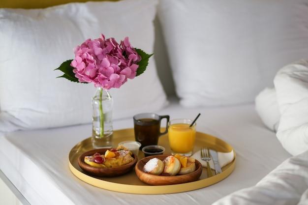 Prima colazione in albergo. colazione a letto con un fiore. caffè, succo di frutta e cheesecake a letto. mangia a letto. fine settimana pigro.