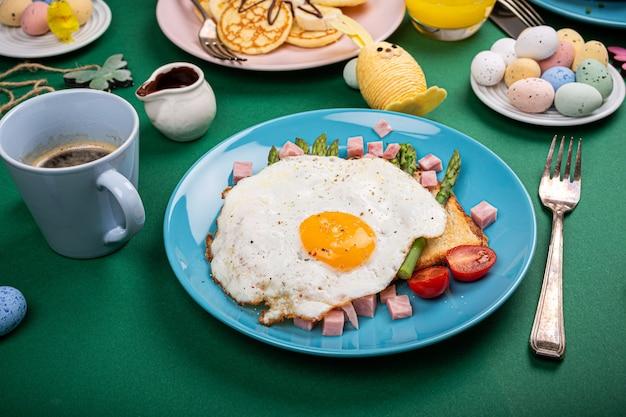 Colazione o pranzo con uovo fritto, pane tostato, asparagi verdi, pomodori e pancetta sul piatto blu