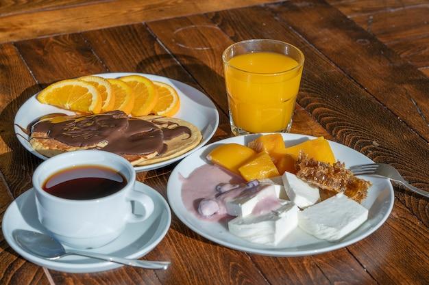 Colazione a base di molti piatti e bevande su un tavolo di legno, primo piano. concetto di cibo