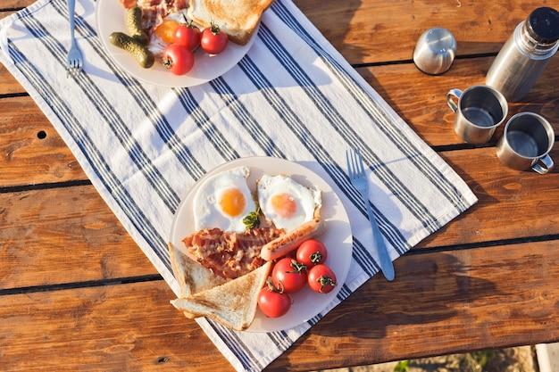 Colazione nella natura uova fritte con bacon tostato fritto e caffè caldo da un thermos