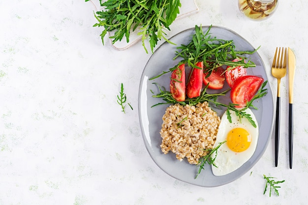 Porridge di farina d'avena per la colazione con uovo fritto, pomodori, rucola. cibo salutare. vista dall'alto, sovraccarico, copia dello spazio
