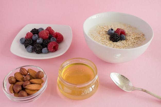 Colazione: farina d'avena con frutti di bosco, miele e noci su sfondo rosa