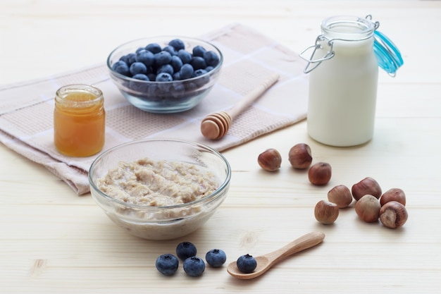 Colazione a base di farina d'avena con mirtilli, miele, latte e nocciole