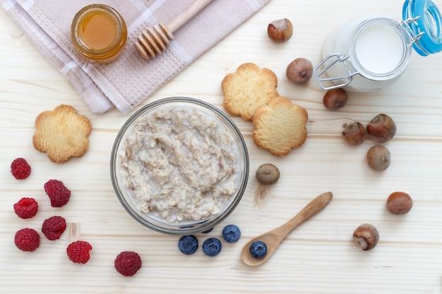 Colazione a base di farina d'avena con mirtilli, lamponi, biscotti, miele, latte e nocciole