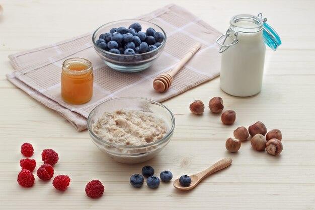 Colazione di farina d'avena con mirtilli, lamponi, miele, latte e nocciole