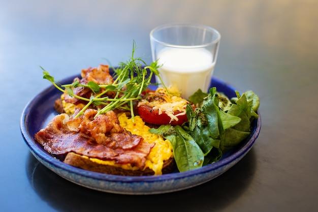 Colazione su un piatto di pancetta insalata di uova pomodoro formaggio un bicchiere di yogurt
