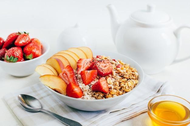 Farina d'avena porridge di colazione con cereali muesli fragole pesche miele in un piatto bianco sullo sfondo di una teiera bianca e ciotole con miele su un piatto bianco