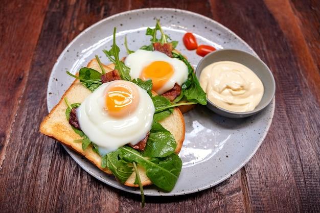 Panino per la colazione con uova, pancetta e panna acida in un piatto sul tavolo di legno