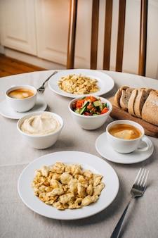 Colazione. uova strapazzate o frittata, hummus, caffè, insalata di verdure, pane. tavolo da pranzo