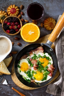 Colazione uova strapazzate con pancetta caffè bacche biscotti noci e succo vista dall'alto