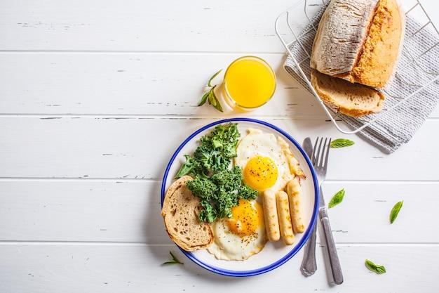 La colazione viene servita con uova fritte, insalata, muffin e succo d'arancia sul tavolo di legno bianco.