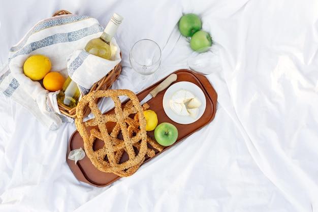 Colazione all'alba, sull'erba lenzuolo bianco con vassoio con formaggio e vite, pane secco, mela, limone. umore romantico, concetto estetico di stile di vita lento, vista dall'alto