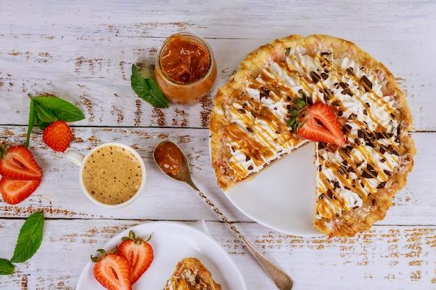 Torta dolce colazione con fragole e tazza di caffè latte sulla tavola di legno