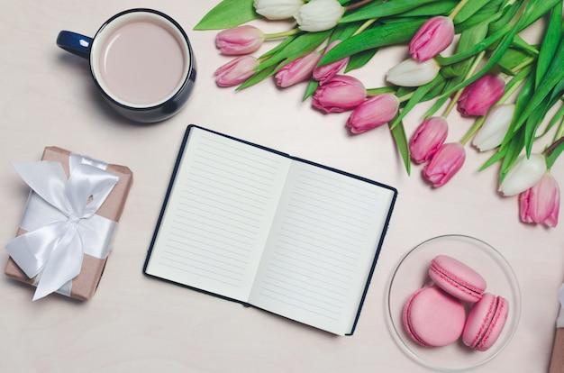 Colazione sul tavolo composizione piatta con fiori, un blocco note una tazza di caffè e dolci.