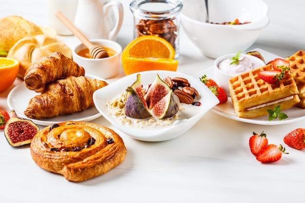 Tavolo per la colazione con fiocchi d'avena, waffle, cornetti e frutta.