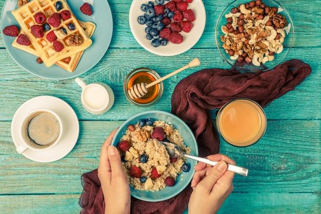 Tavolo per la colazione con cialde, farina d'avena, cereali, caffè, succo di frutta e frutti di bosco freschi. colazione salutare