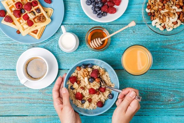 Tavolo per la colazione con cialde, farina d'avena, cereali, caffè, succhi di frutta e frutti di bosco freschi