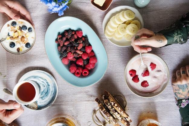 Tavolo per la colazione con yogurt e frutti di bosco freschi
