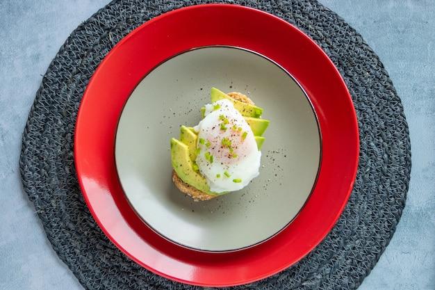 Colazione di toast con avocado e uovo in camicia