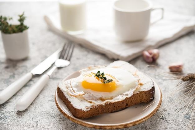 Colazione a base di pane tostato con uovo fritto su un piatto, fuoco selettivo