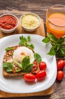 Pane tostato per colazione con uovo in camicia, salsa di pomodoro, basilico e parmigiano su legno rustico