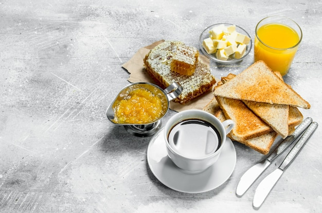 Colazione. pane tostato con burro, miele e marmellata di arance. su una superficie rustica.