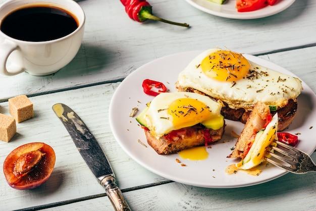 Toast per la colazione con verdure e uovo fritto sul piatto bianco, tazza di caffè e alcuni frutti su legno