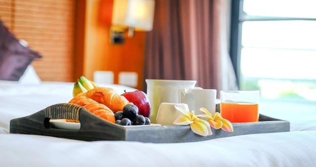 Colazione in un vassoio sul letto nella camera d'albergo di lusso pronta per il viaggio turistico.