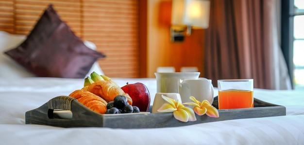 Colazione in un vassoio sul letto in un hotel di lusso