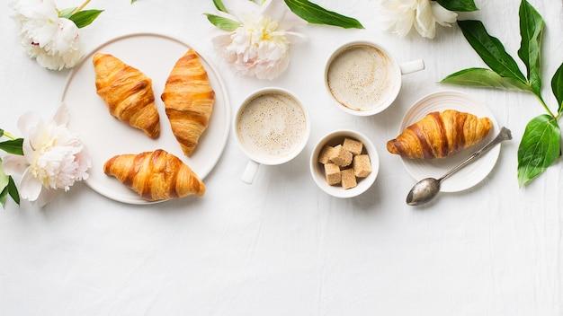 La colazione sul piatto bianco laici. croissant con tazza di caffè e fiori
