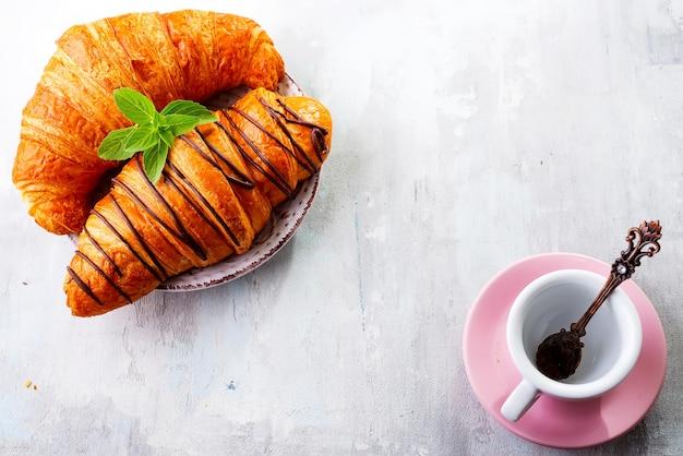 Prima colazione sulla superficie di legno bianca con croissant e caffè