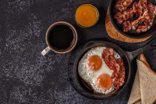 Colazione con pancetta, uovo fritto, caffè e succo d'arancia
