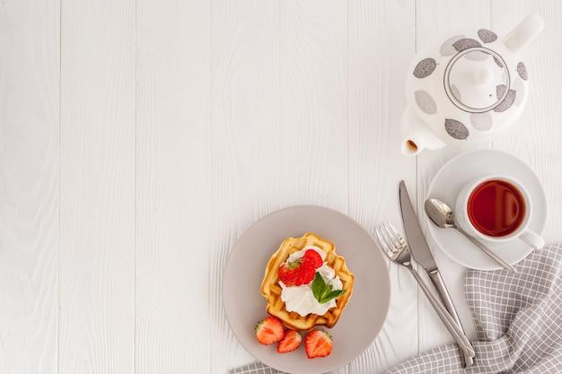 Prima colazione con cialde belghe su legno bianco