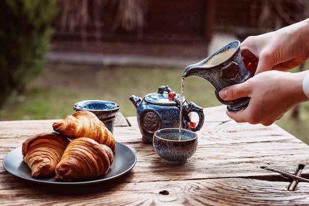 Colazione con tè cinese e pasticceria fresca, croissant aromatici al burro. le mani delle donne versano il tè. cerimonia del tè.