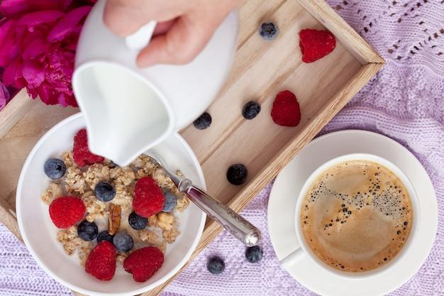Colazione con caffè, muesli, frutti di bosco e latte