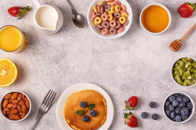 Colazione con anelli di cereali colorati, frittelle, frutta, latte, succo di frutta