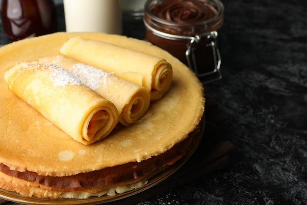 Colazione con crepes con pasta di cioccolato sul tavolo smokey nero
