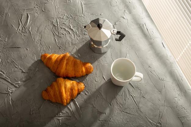 Colazione con croissant e caffè nero. pasto mattutino e concetto di colazione. vista dall'alto.
