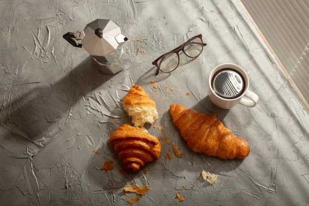 Prima colazione con croissant sul tagliere e caffè nero. pasto mattutino e concetto di colazione. vista dall'alto.