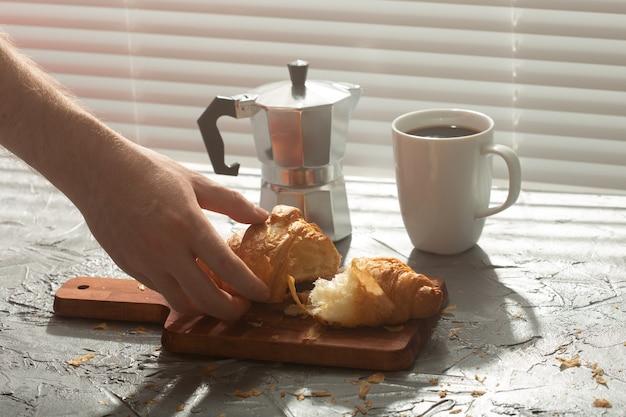 Prima colazione con croissant sul tagliere e caffè nero. pasto mattutino e concetto di colazione.