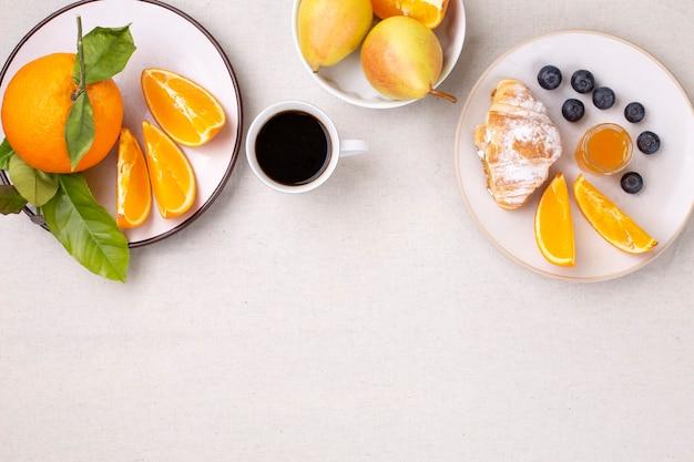 Colazione con una tazza di caffè, croissant freschi, marmellata e mirtilli maturi e arance succose, pere su sfondo bianco, piatto, copia spazio.