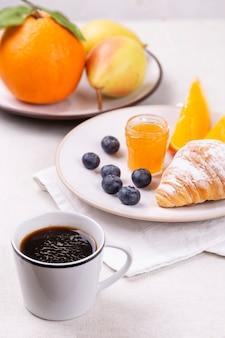 Colazione con una tazza di caffè, croissant freschi, mirtilli maturi e arance succose su sfondo bianco, verticalmente.