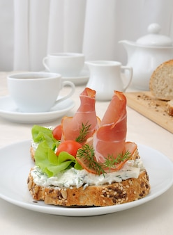 Colazione con una tazza di caffè e un panino di pane integrale con ricotta e prosciutto