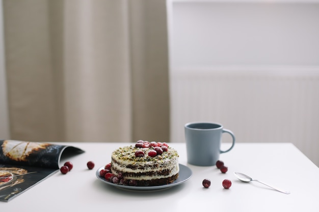 Colazione con una tazza di tè e una torta con spinaci e crema decorata con mirtilli rossi freschi sul tavolo bianco