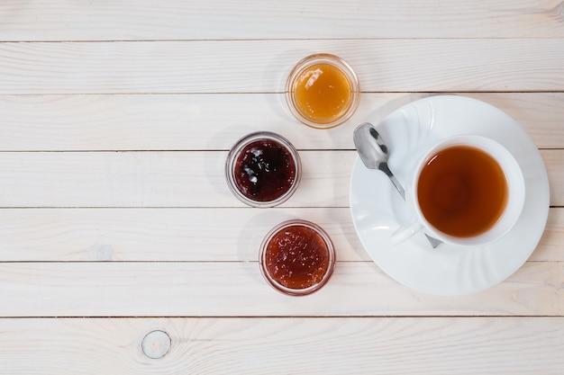 Colazione con tazza di tè e marmellata su fondo bianco in legno rustico, vista dall'alto
