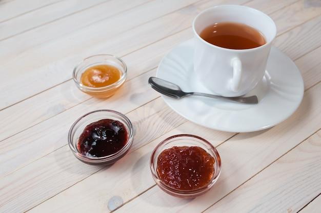 Colazione con una tazza di tè e gelatina di fragole, ribes e albicocche o marmellata su fondo bianco in legno rustico, primo piano